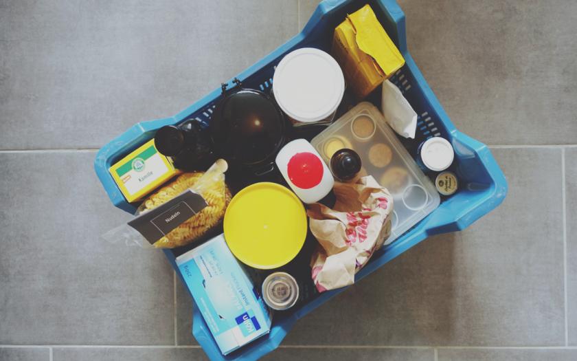 Beitragsbild // Lowwaste im Urlaub // Das Bild zeigt eine gepackte Kiste mit Lebensmitteln, verpackt und teilweise auch OVP mit und ohne Plastikpackungen.